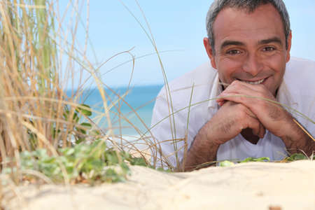 35 years: mature man resting at the beach Stock Photo
