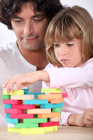 Father and daughter building a tower of blocks photo