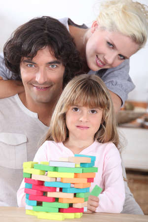Couple playing a stacking game with their daughter photo