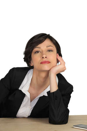 assertive: Attractive businesswoman sitting at her desk Stock Photo