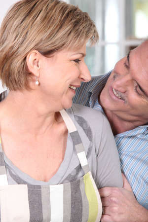 Couple in their fifties laughing in the kitchen photo