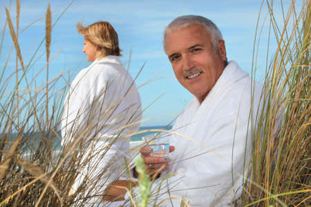 Couple at the beach in robes photo