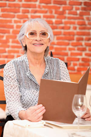 65 years old: Woman reading a menu in a restaurant Stock Photo