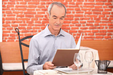 Man looking at a menu in a restaurant photo