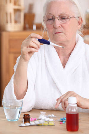 sickly: Elderly woman with a thermometer