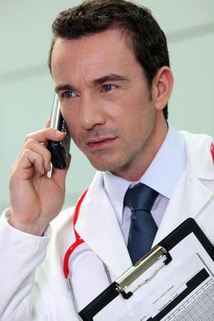 young doctor talking on his cell phone photo