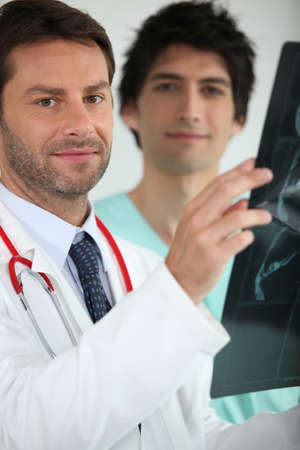 Two medics examining an X ray photo