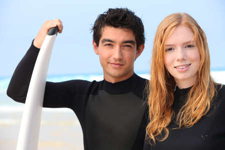Two teenagers wearing wetsuits stood with surfboard photo