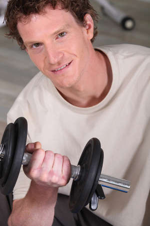 Sporty man lifting barbell photo