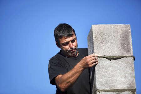 erecting: mason erecting a stone block wall Stock Photo