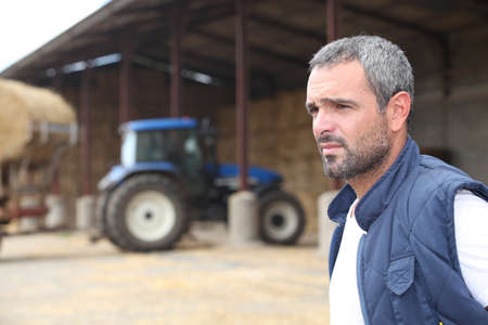 Farmer standing in front of a barn containing a tractor photo