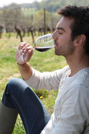 beau jeune homme: Homme assis à boire du vin rouge Banque d'images