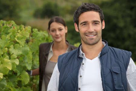 joven agricultor: Joven agricultor estaba con la mujer en la vi�a Foto de archivo