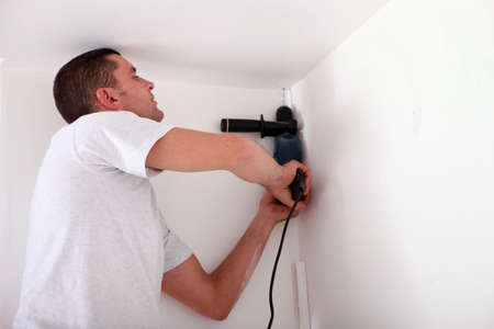 remount: Man drilling a ceiling