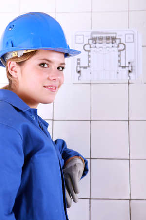 jumpsuite: young woman wearing a blue jumpsuite in front of an electrical schema