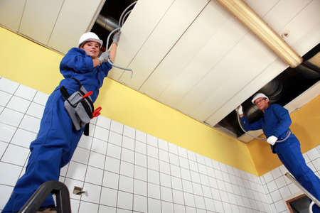 two electricians working in a building photo