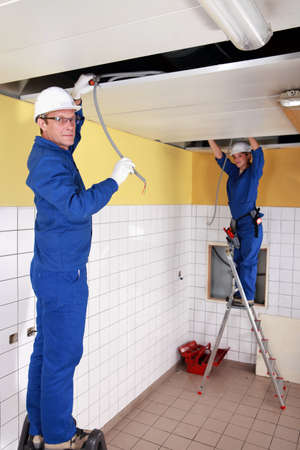 jumpsuite: two electricians working on the ceiling Stock Photo