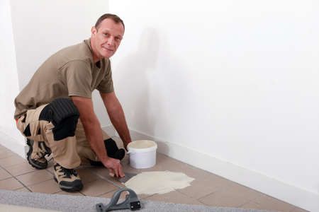 adherent: Carpet fitter spreading adhesive on a tiled floor