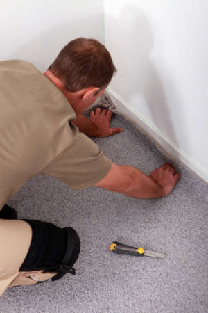 fitting: Man fitting carpet into the corner of a room