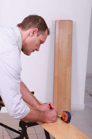 Tradesman marking a measurement on a wooden plank photo