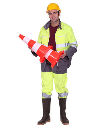 road worker: road worker holding a traffic cone Stock Photo