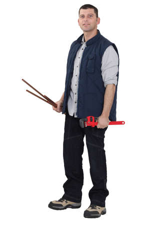 Man holding a pipe wrench and copper pipes photo