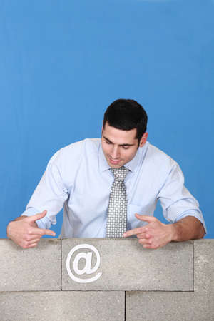 unfinished: Man pointing towards at symbol stuck to wall Stock Photo