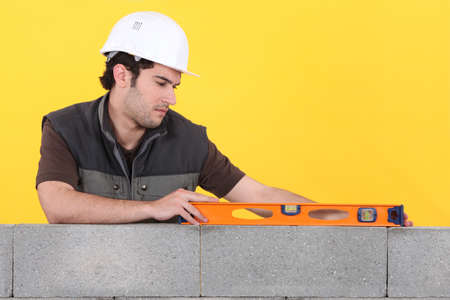 Man with spirit level checking wall photo