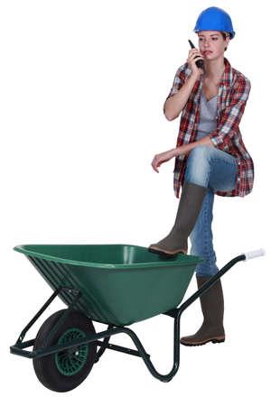 cb: Woman stood with empty wheelbarrow Stock Photo