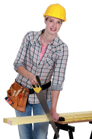 young female carpenter using saw Stock Photo - 12052981