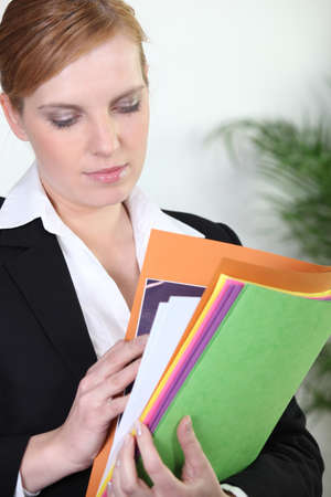 reviewer: Redheaded businesswoman carrying paperwork Stock Photo