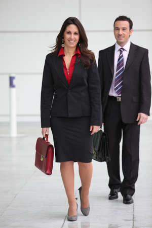 skirt suit: Couple in suits carrying briefcases