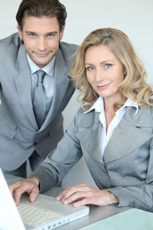 A businessman and a businesswoman working in front of a laptop and looking at us. Stock Photo - 12030671