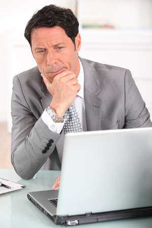 Businessman confused by his laptop photo