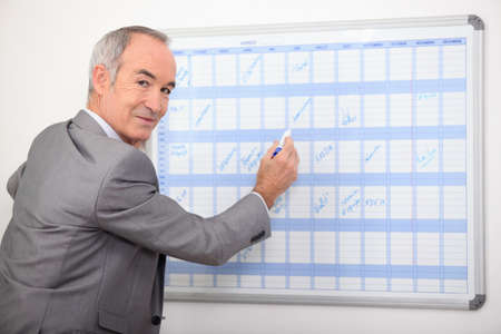 straight faced: Older businessman writing on a wall planner