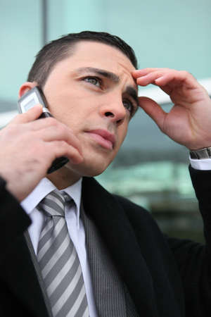 preoccupied: close-up shot of young businessman on the phone looking preoccupied Stock Photo