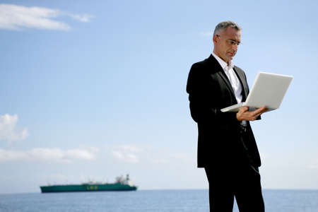 Businessman using his laptop at the coast