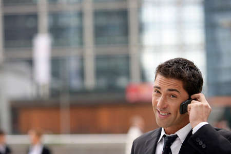 Yuppie businessman making a call outside office Stock Photo - 12007896
