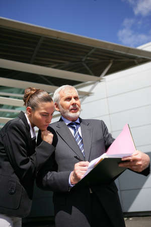 Businesspeople reviewing paperwork outside photo