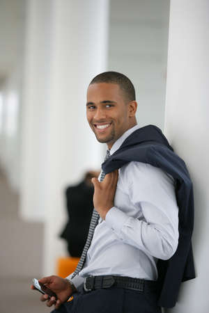 Attractive businessman leaning against wall with his jacket over his shoulder photo