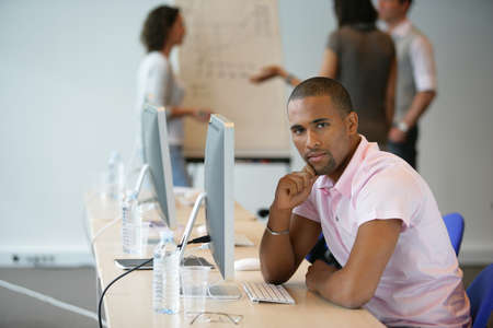 african business: Businessman sat at computer with colleagues in the background