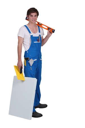 tablaroca: Comerciante joven posando con sus herramientas y materiales Foto de archivo