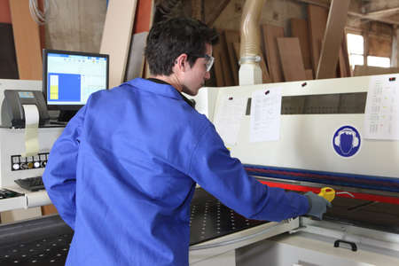 factory worker: Young worker operating factory machine