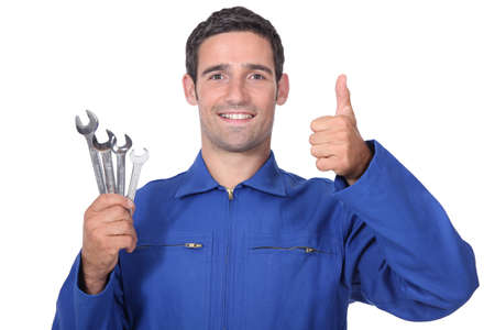 all smiles: head and shoulders portrait of plumber holding wrenches all smiles Stock Photo