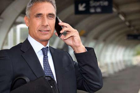 calling businessman: Businessman waiting for a train on the platform
