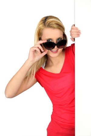 peering: Woman peering over oversized sunglasses Stock Photo