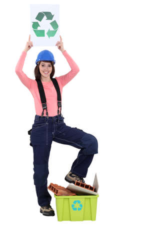 female bricklayer holding recycling logo against white background photo