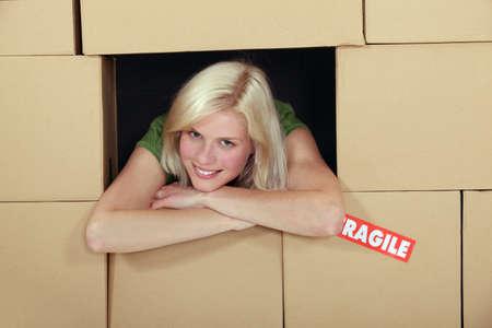 cajas de carton: La mujer se puso en medio de cajas de cart�n Foto de archivo