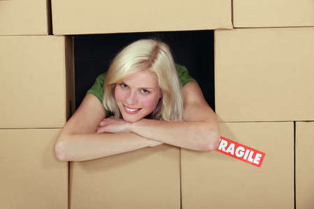storage compartment: Woman stood amongst cardboard boxes