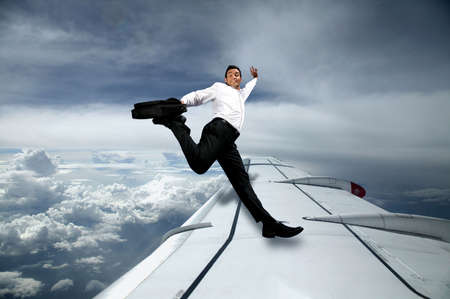 keeping: Man in suit jumping on the wing of an airplane Stock Photo